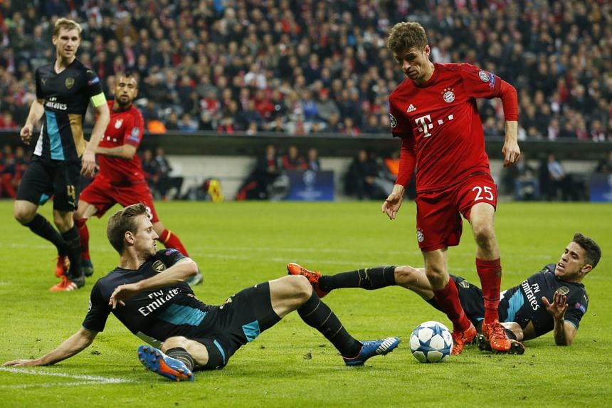 Thomas Mueller (No. 25) shows balance and ball-control skill to stay on his feet while Arsenal's Nacho Monreal (left) and Gabriel Paulista hit the turf during the Champions League Group F game at Allianz Arena, Munich on Wednesday. Mueller scored a b
