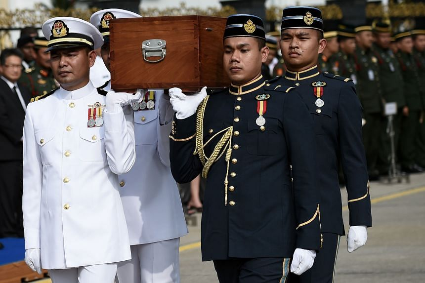 Malaysian troops bearing the presumed remains of the US airmen in a sombre ceremony in Kuala Lumpur yesterday. The airmen were on a flight to Malaysia on Nov 27, 1945, but never reached their destination.