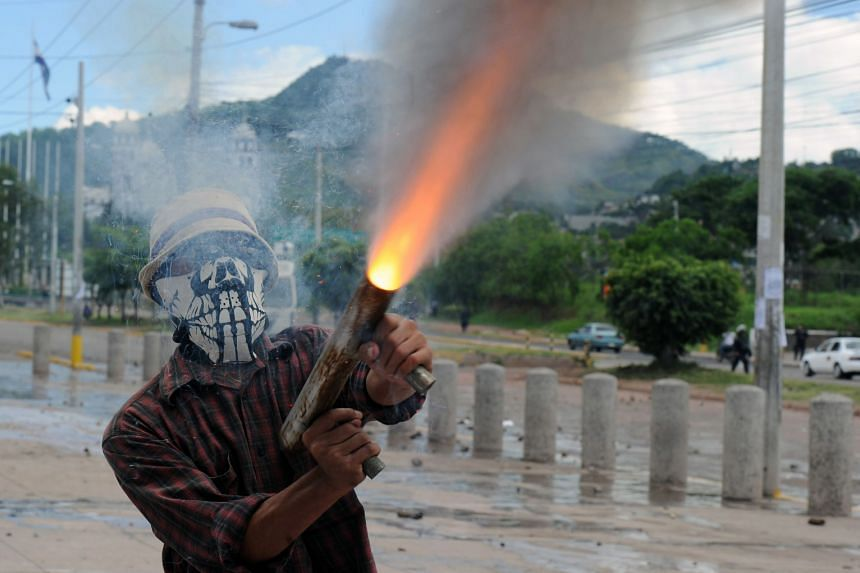 A student from the National Autonomous University of Honduras firing a homemade gun in the capital - Tegucigalpa - during clashes with police this week. The protesters were demanding a United Nations investigation into alleged government corruption.