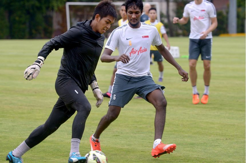 """Madhu Mohana (right, with Izwan Mahbud) does not follow European football - even once referring to Shinji Kagawa as """"the guy who played for Manchester United""""."""