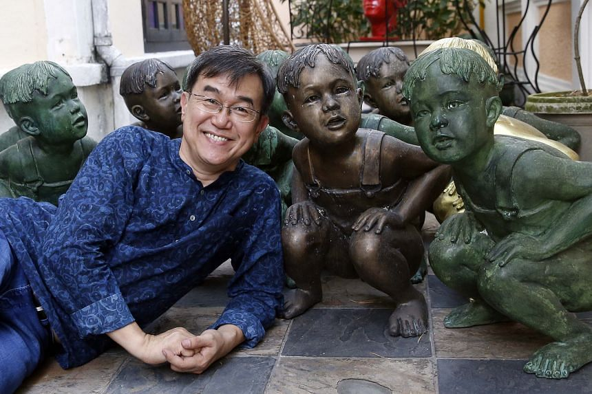 """Mr Sim, with the sculptures of a boy squatting down, in his Katong home. He said the boy represents his three-year-old self having to do his business in the open in the kampung he used to live in, adding: """"We've come a long way since then."""""""