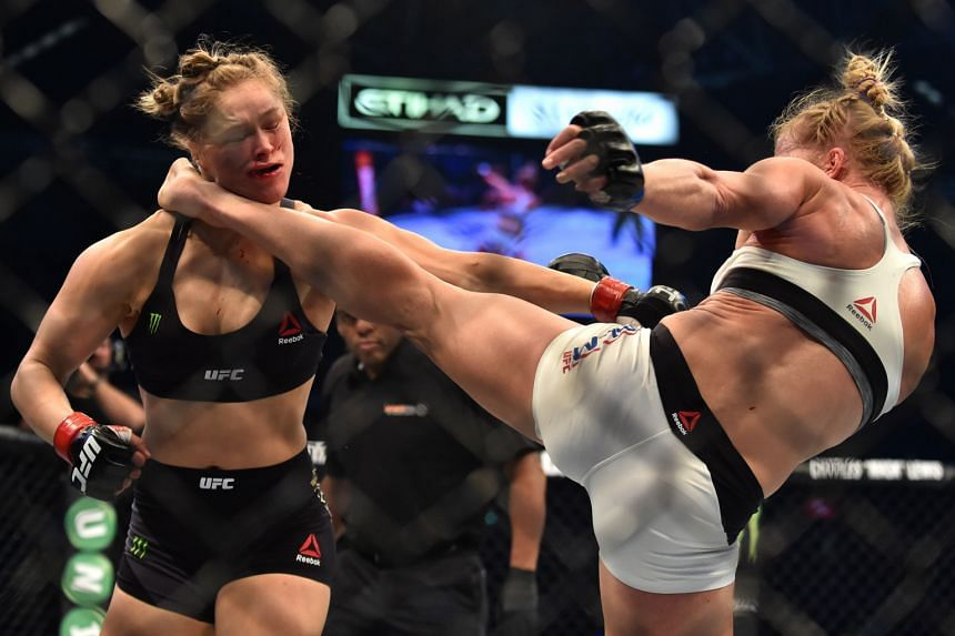 Holly Holm (right) landing a kick to the neck to knock out bantamweight defending champion Ronda Rousey in the UFC title fight in Melbourne yesterday.