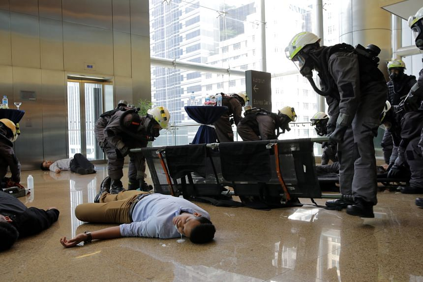 In the second simulated scenario at Esplanade Park, office workers were affected by the explosion. SCDF staff cutting open a victim's clothes for the decontamination process after a chemical agent attack. In the first simulation, office workers at On
