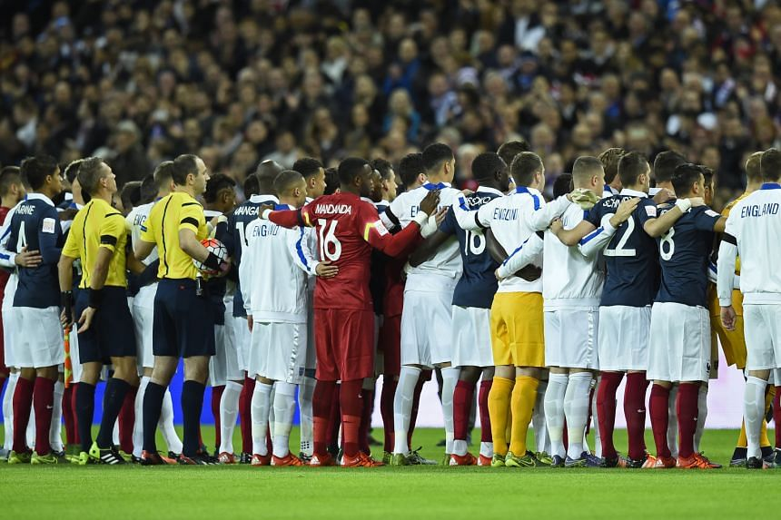 The two teams showing solidarity by mixing their line-ups during the national anthems.