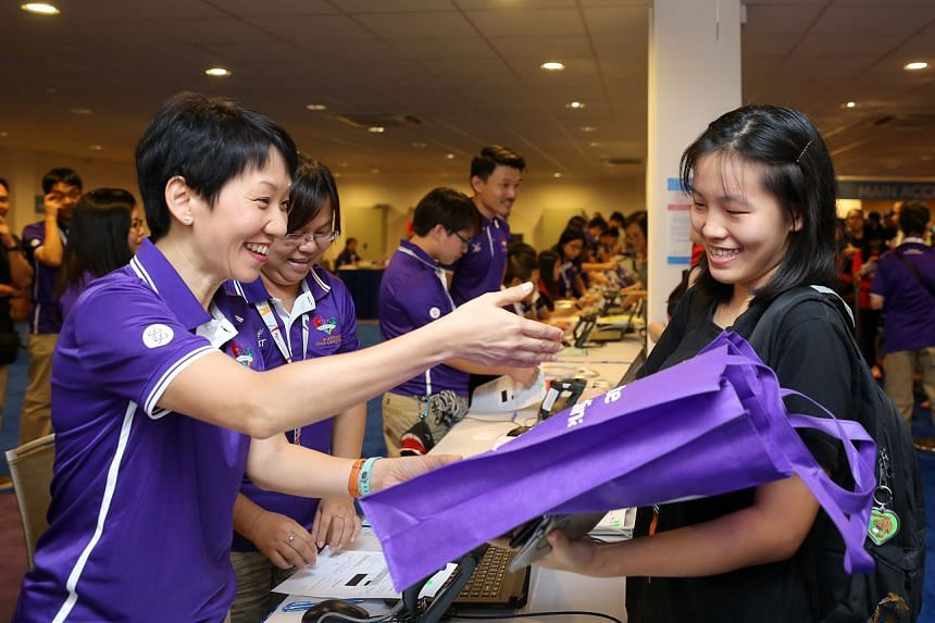 Minister for Culture, Community and Youth Grace Fu (left) handing out a uniform pack to an Asean Para Games volunteer yesterday.