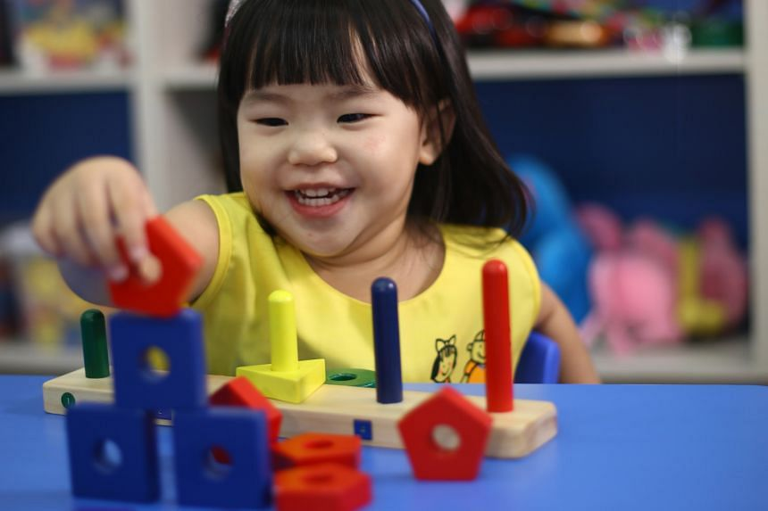 A child at a Star Learners pre-school playing with a set of geometric sorting blocks. Pre-school experts say it is important for children to explore, as this helps them develop their creativity.