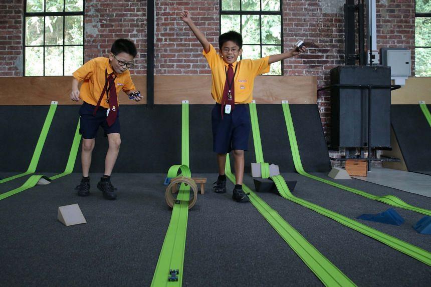 Yumin Primary School pupils Jack Lim (left) and Brasen Mavis Sayson, both nine, having fun racing toy cars at Playeum.