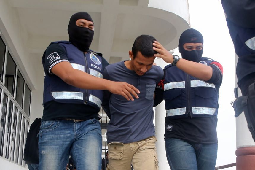 The Malaysian police have detained more than 100 suspected Malaysian militants, including former commando Muhammad Adibzakir Zahri (centre), who was charged in September with encouraging membership in ISIS.