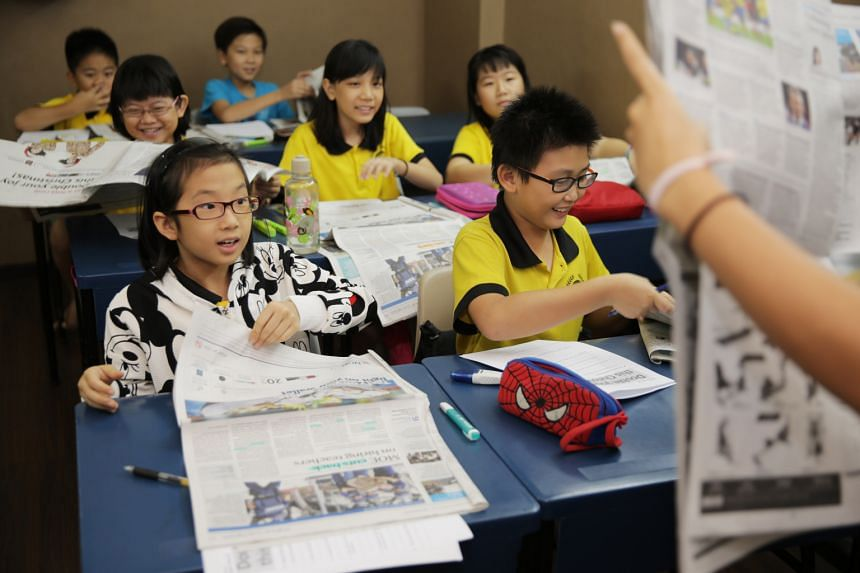 Fyndy Siom Wen Jing (front) and her friends at a newspaper reading session at Groworld Learning Tuition Centre, where pupils are encouraged to think more in depth before they answer questions.