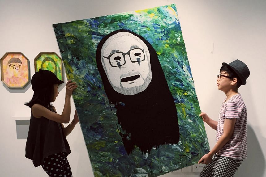 Siblings Aira (far left) and Renn Lim taking down an artwork from their exhibition at the National Gallery Singapore's Gallery & Co cafe.