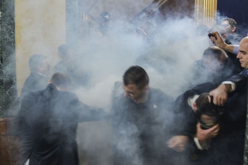 Members of Parliament leaving the chamber after tear gas was released by opposition lawmakers at Kosovo's Parliament in Pristina on Monday. It is the latest in a series of long-running protests against government agreements made with Serbia.