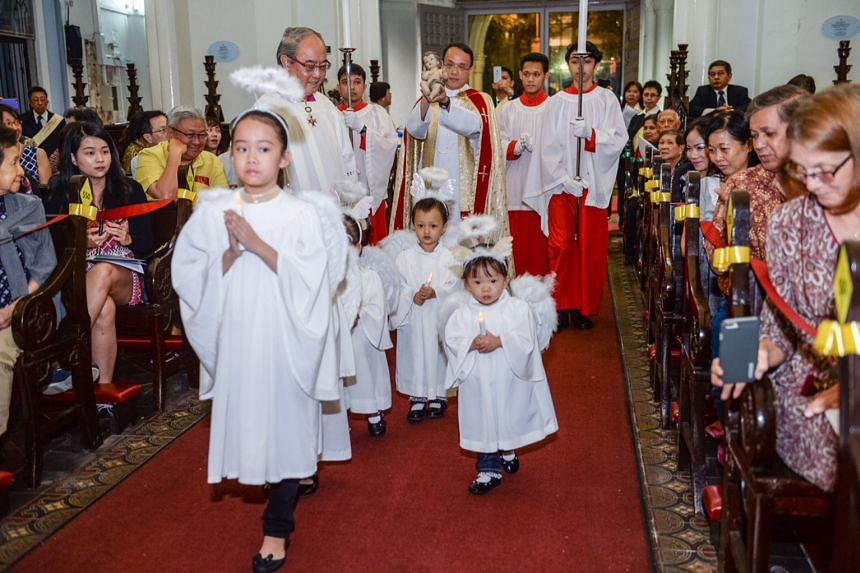 "Father Ignatius Yeo, led by little ""angels"", carrying a statue of the baby Jesus into St Joseph's Church. Looking on as the children trooped past is conductor and director of the Cathedral Choir of the Risen Christ, Dr Peter Low, who composed a carol"