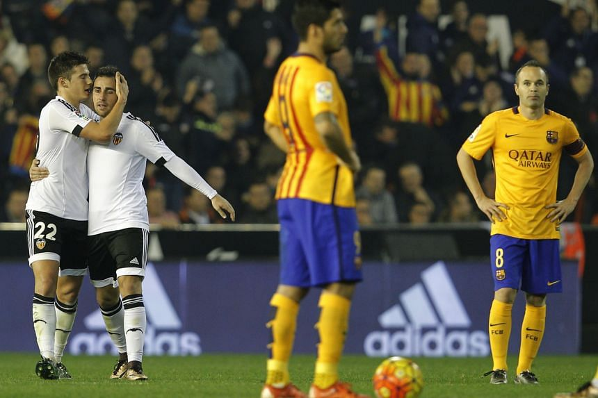 Valencia's Santi Mina (left) celebrating his goal with team-mate Paco Alcacer, who set up the equaliser for the home team. Luiz Suarez (3rd from left) had put Barcelona, who wasted several chances, ahead.