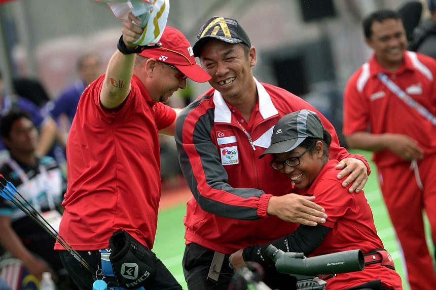 Syahidah Alim (sitting) celebrating her second archery gold medal yesterday. She won the women's individual compound event and partnered Robert Fuchs (left) to capture the mixed team title as well.