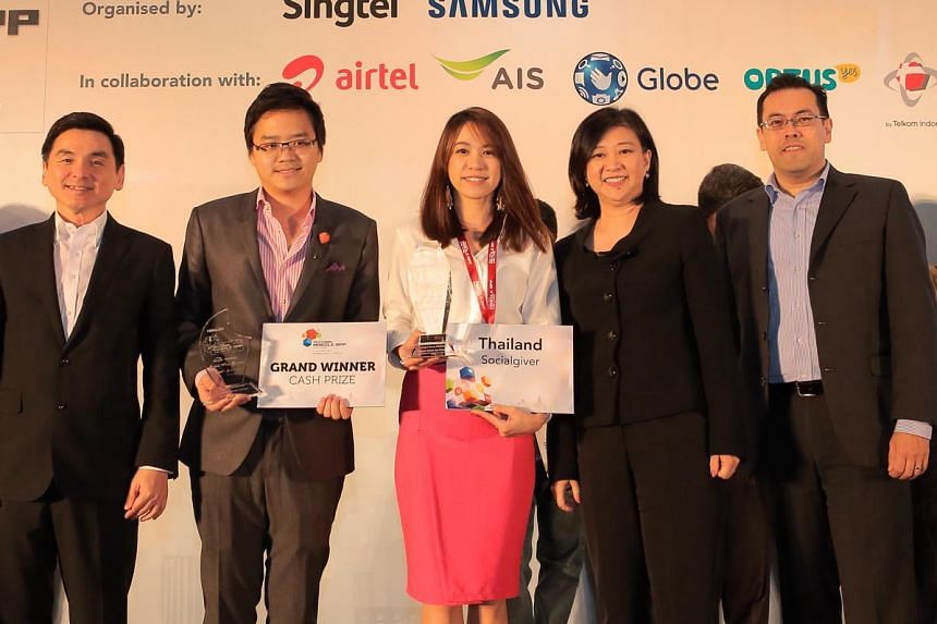 At the Singtel-Samsung regional mobile app challenge in Jakarta were (from left) Mr Somchai Lertsutiwong, CEO of AIS, Mr Arch Wongchindawest and Ms Aliza Napartivaumnuay from Socialgiver, Ms Chua Sock Koong, group CEO of Singtel, and Mr Edgar Hardles