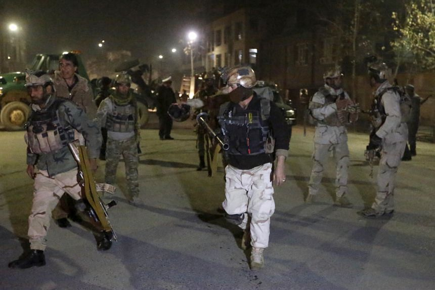 Members of the Afghan Crisis Response Unit arriving at the site of a Taleban attack in Kabul yesterday. Insurgents launched an attack on a Spanish embassy compound there, officials said.