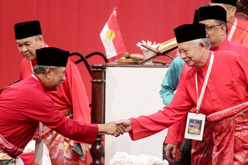 Umno president and Malaysian Prime Minister Najib Razak (right) shaking hands with former deputy prime minister and Umno deputy president Muhyiddin Yassin during the party's general assembly. The leader's closing speech was directed at dissenters led