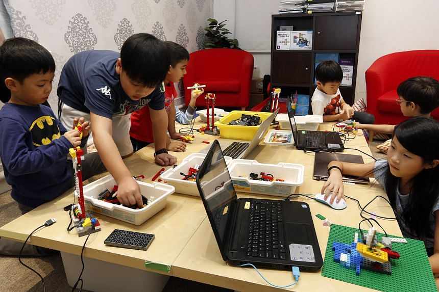 Five-year-old Christian Ong (far left) is interested in the mechanics of things. Here, he and fellow course mates learn how to program a robot launch pad using Lego pieces during a holiday workshop at In3Labs.