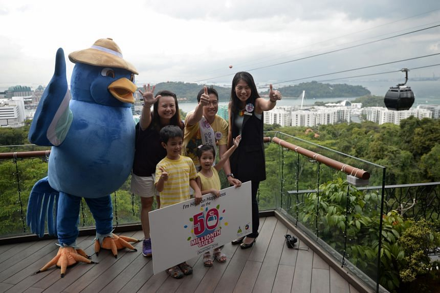Mr Chuan Kai Liang, wife Caroline and children Julian and Olivia marking their winning moment with a photograph. With them is general manager Suzanne Ho (far right) of Mount Faber Leisure Group.