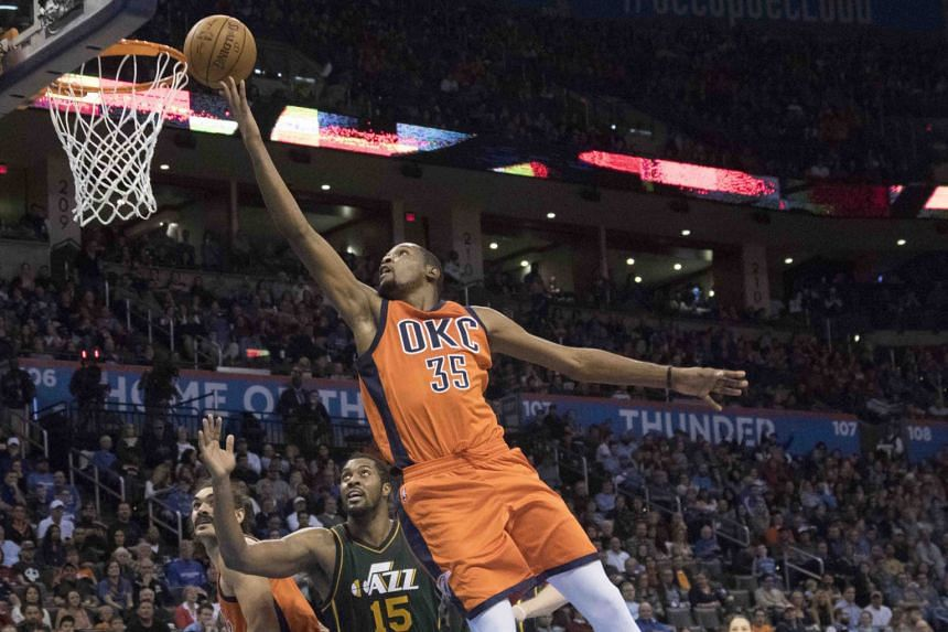 Oklahoma City Thunder's Kevin Durant (front) sailing past Utah Jazz's Derrick Favors for two points during the third period at the Chesapeake Energy Arena. The Thunder won 104-98 in overtime.