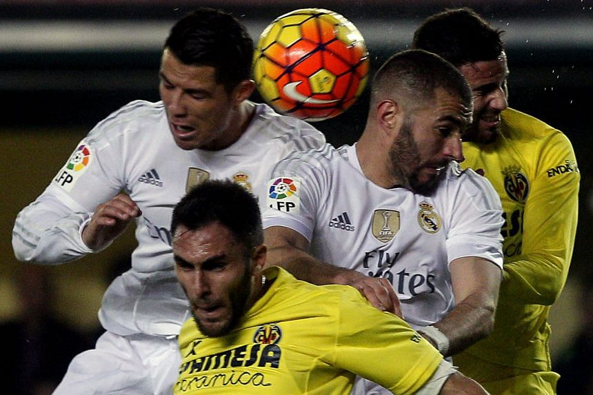 Real Madrid forwards Cristiano Ronaldo (left) and Karim Benzema (centre) vying for the ball in a tight aerial tussle against Villarreal defenders Victor Ruiz (front) and Mateo Musacchio (right). Real suffered a surprise 0-1 loss in the La Liga encoun