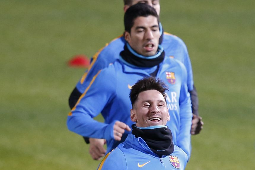 Barcelona players Lionel Messi (front) and Luis Suarez running during a training session ahead of their Club World Cup semi-final match tomorrow against Luiz Felipe Scolari's Guangzhou Evergrande in Yokohama.