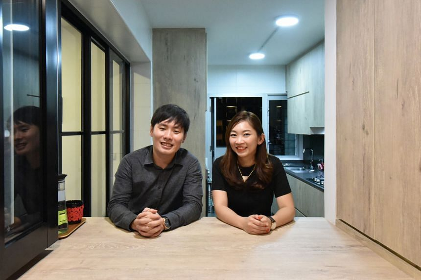 Owners Ow Khai Wan and Kimberly Chow (both left) housekeep on weekends to keep clutter at bay in their five-room HDB flat (above).