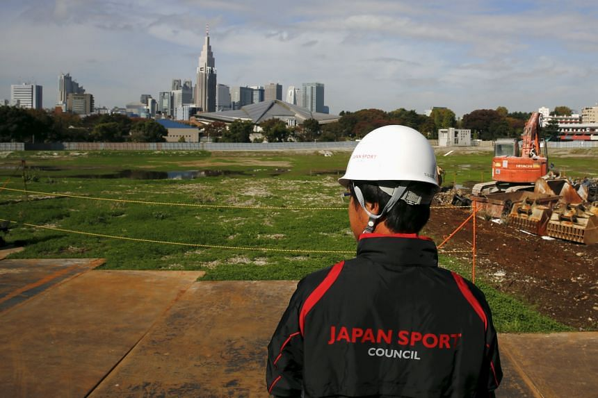 An official overlooks the empty site of the planned national stadium, the centrepiece of the Tokyo 2020 Olympics.