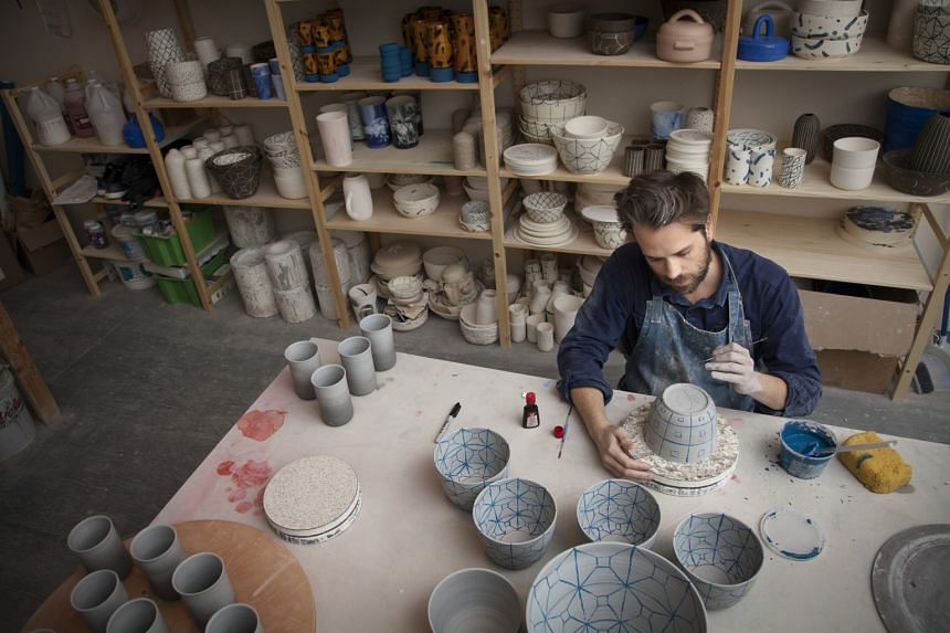 Ceramic containers at trendsetting boutique Still House (left) in Manhattan and at Primary Essentials (below right), a shop in Brooklyn; and designer Forrest Lewinger (below left) of Workaday Handmade sculpting at his studio in Queens.