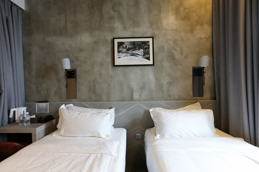 Grey cement-washed walls in some of the rooms (above) and an all-concrete check-in desk complement the industrial-chic theme of the hotel.