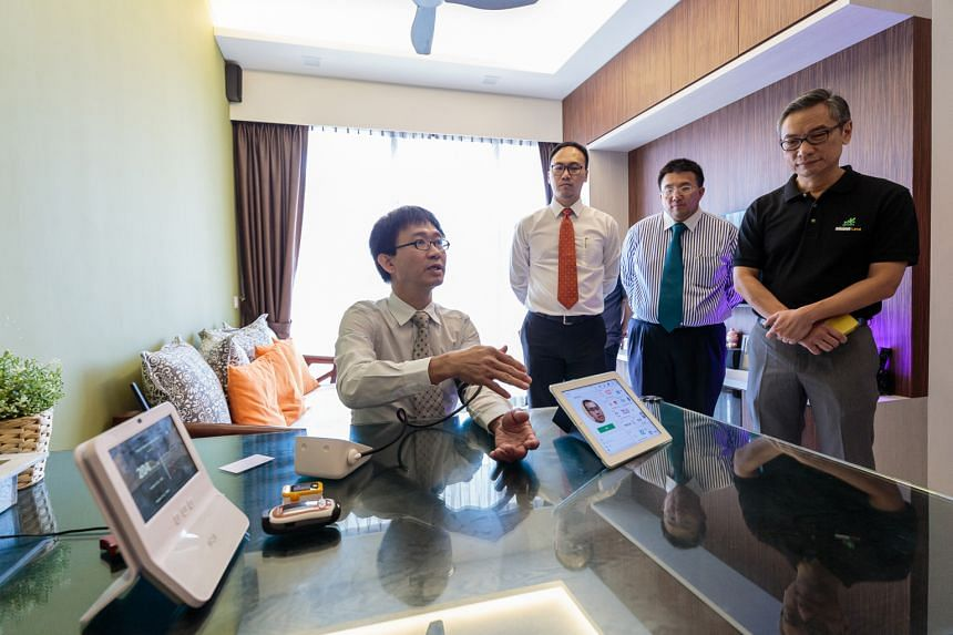 A Napier Healthcare representative (seated) shows (from right) Keppel Land property management general manager Lim Tow Fok and M1 chief product development and corporate solutions officer Willis Sim how the healthcare system used in the pilot program
