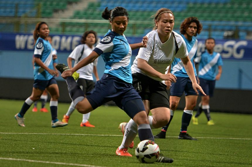 The Police Sports Association's Fatin Afiqah (left) attempting a shot against Warriors FC during their 2015 Women's Challenge Cup final at Jalan Besar Stadium yesterday. Police won 2-0 thanks to goals from Manami Fukuzawa (36th) and Fatin (44th). The