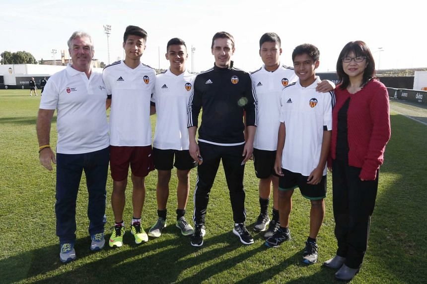 Young footballers from Singapore posing for photos with Valencia football club head coach Gary Neville (black shirt) and club chairman Chan Lay Hoon (right) last Friday. They are part of a 17-strong group of student-footballers - all of whom are unde