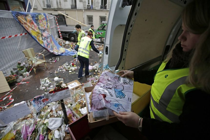 City archivists collect the notes, poems and drawings left at an informal memorial in front of Casa Nostra pizzeria, one of the sites of the Nov 13 shooting attacks in Paris, France.