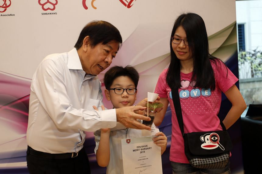 Greenwood Primary School pupil Chang Cheng Jun took home an Edusave Merit Bursary award yesterday. He and his mother also got a photo with Sembawang GRC MP Khaw Boon Wan, who gave out the awards.