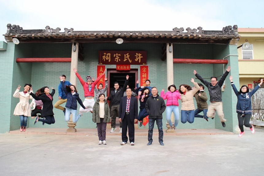 Mr Hooy (centre) with son Eric (standing on his left), daughter Serene (on his right) and the association's youth members at the ancestral hall in Xiheng village in Zhongshan.