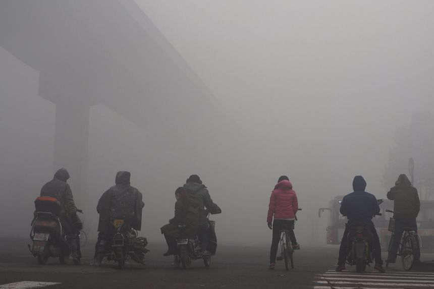 Residents of Shijiazhuang, Hebei province, waiting at a traffic intersection amid heavy smog on Dec 10. The province, a major steel manufacturer and heavy coal user, contributes to much of the pollution that blights Beijing.