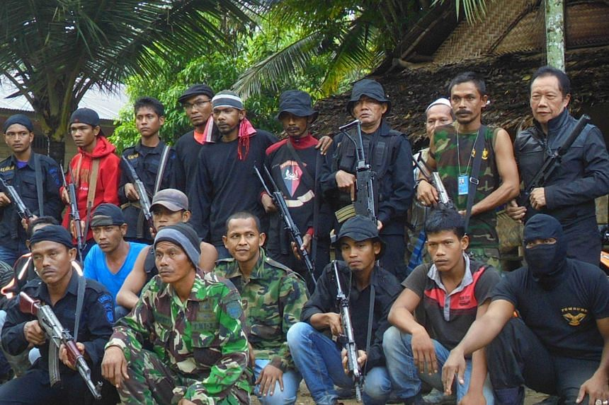 Indonesian intelligence chief Sutiyoso (right, second row) and rebel leader Din Minimi (second from right, second row) with members of the rebel group that surrendered in Ladang Baro, East Aceh, on Dec 29 last year.