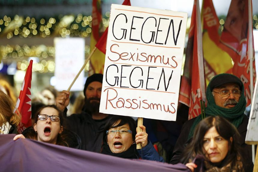 """Protesters on Tuesday marching through the main train station near where the assaults took place in Cologne, Germany. The placard reads """"Against Sexism - Against Racism"""". Cologne police say they believe several hundred men were involved in the violen"""