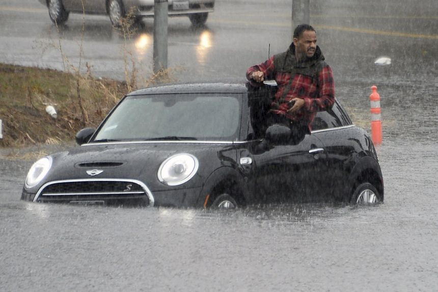 A driver climbing through a window of his car after becoming stranded on a flooded road in the Los Angeles neighbourhood of Van Nuys on Tuesday. Several more El Nino storms are set to hit California in the coming weeks.