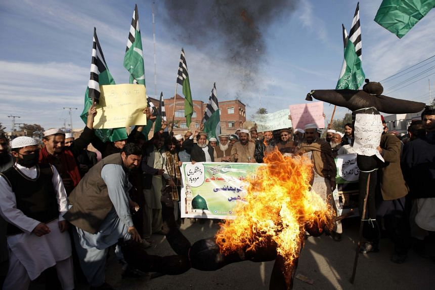 Pakistani supporters of Rah-e-Haq religious party in Peshawar burning an effigy representing Iran, Israel and the US at a rally on Tuesday in favour of Saudi Arabia's execution of Shi'ite cleric Nimr al-Nimr.