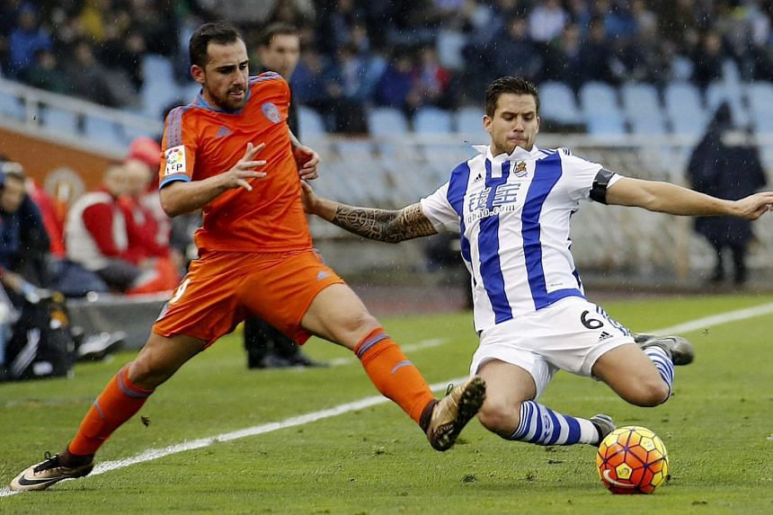 Valencia striker Paco Alcacer (left) fighting for the ball with Real Sociedad defender Inigo Martinez during their La Liga match. Gary Neville's side lost 0-2, leaving him still seeking a win in the league.