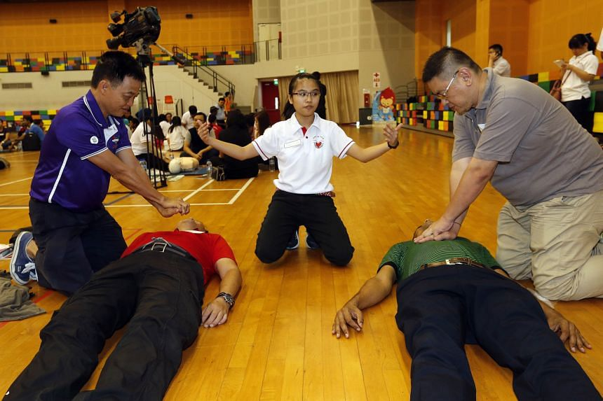 MsTracy Koh (centre), 20, teaching Pasir Ris-Punggol GRC residents how to perform cardiopulmonary resuscitation at the launch of the Citizen First Responder course yesterday. Those who complete it will be certified as first aiders for two years.