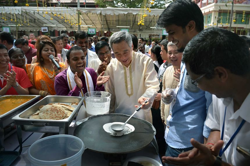 Prime Minister Lee Hsien Loong trying his hand at making Indian snacks like thosai and murukku yesterday at a Pongal celebration at Cheng San Community Club. During the Tamil festival to mark the first harvest of the season, milk, rice and jaggery -