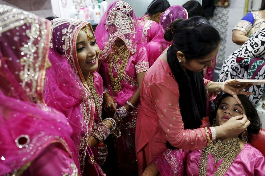 A Muslim bride getting her make-up done, as others wait, at a beauty parlour before the start of a mass marriage ceremony in Mumbai, India, on Wednesday. A total of 12 Indian Muslim couples took their wedding vows at the event organised by a Muslim v
