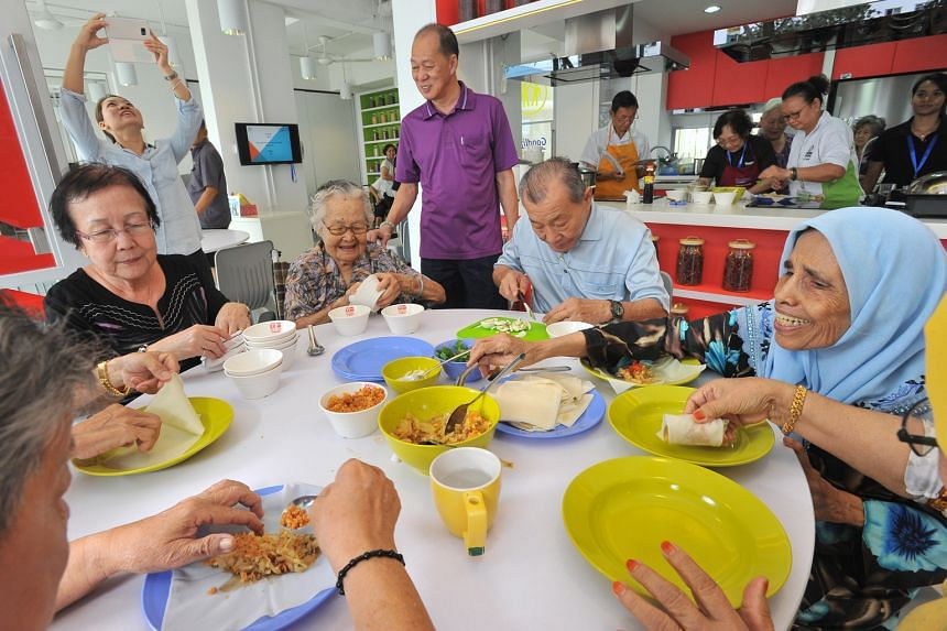 The elderly residents - (from left) Madam Sng Kah Huay, 68; Madam Ing; Mr Looi Hong Teck (standing), 63; Mr Ku and Madam Hindon - preparing popiah at the GoodLife! Makan kitchen on Wednesday.