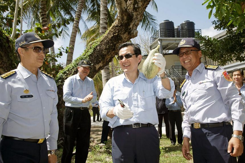 Outgoing Taiwanese President Ma Ying-jeou holding a papaya during his visit to Itu Aba, or Taiping Island, in the South China Sea yesterday. The purpose of the trip was to visit Taiwanese personnel stationed there ahead of the Chinese New Year holida