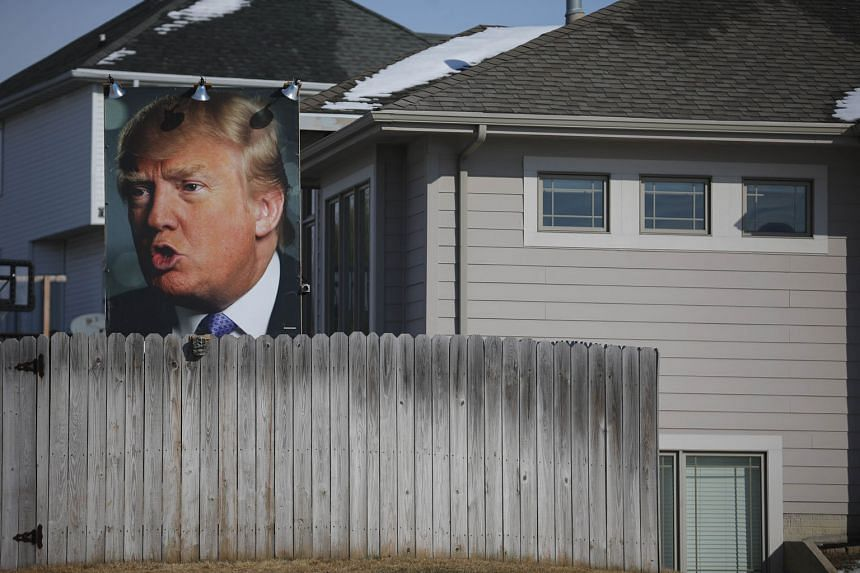 A poster of Mr Trump in a supporter's backyard yesterday in Des Moines, Iowa. Mr Trump would likely have been questioned on his recent suggestion that Iowans, the people whose votes he is courting, are stupid.