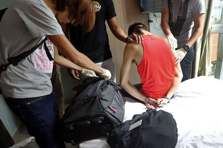 Above: A man, in his 20s, was arrested in a serviced apartment in Geylang following a raid by the Central Narcotics Bureau on Monday. Left: Officers found a pouch containing 0.2g of Ice and an improvised smoking device in the room.