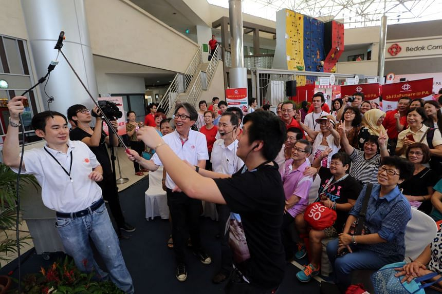 Manpower Minister Lim Swee Say (centre) trying out a selfie stick at the Bedok Community Club event yesterday.